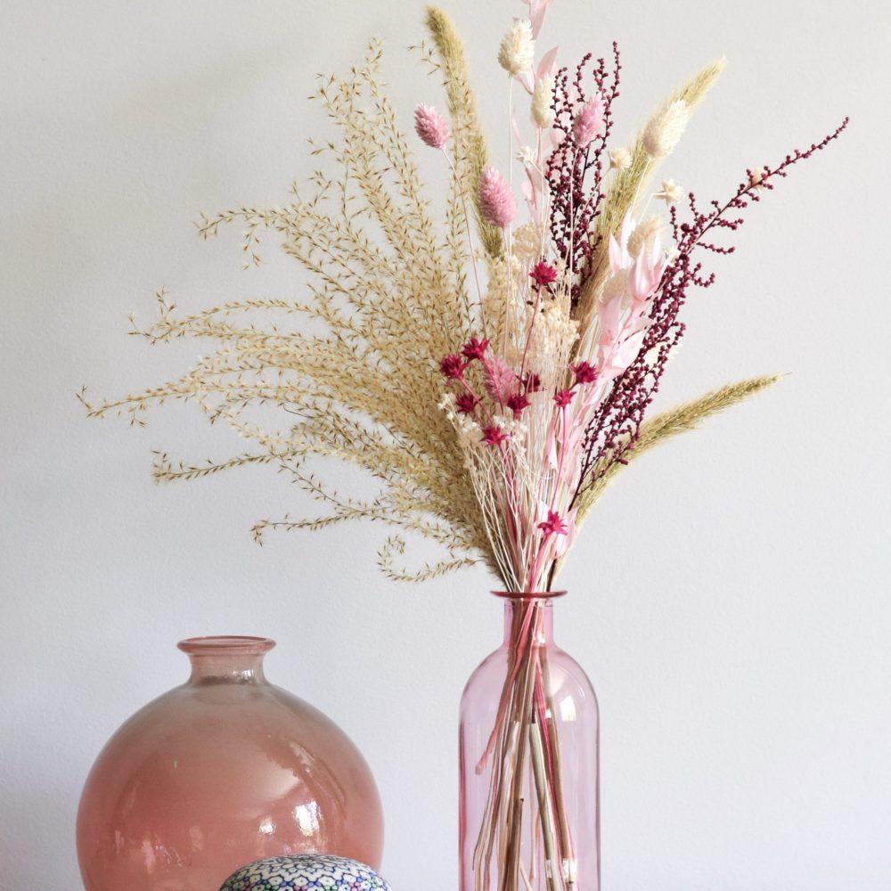 Ramito de flores preservadas en botella de cristal rosa pálido